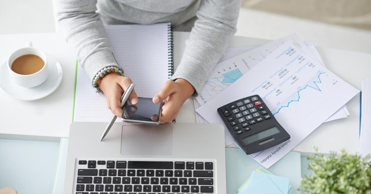 Kvinne sitter foran en PC, bruker kalkulator og regner. Hva koster inbound marketing?